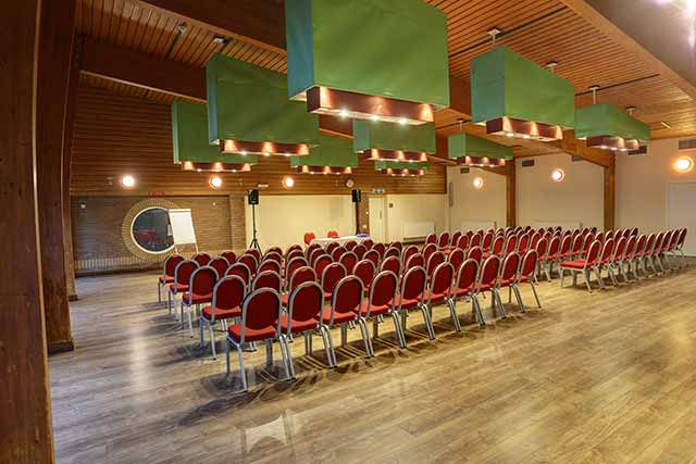 Conference speaking hall photo with rows of red chairs, ample lighting, varnished wooden floor, white board, PA system and speakers