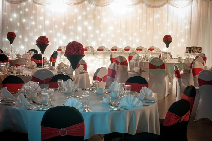 Function Room Dining photo showing possible decorations for upscale parties, events and gala dinners with chair coverings, red floral tablepieces, folded fan napkins, white LED fairy lights, white drapery