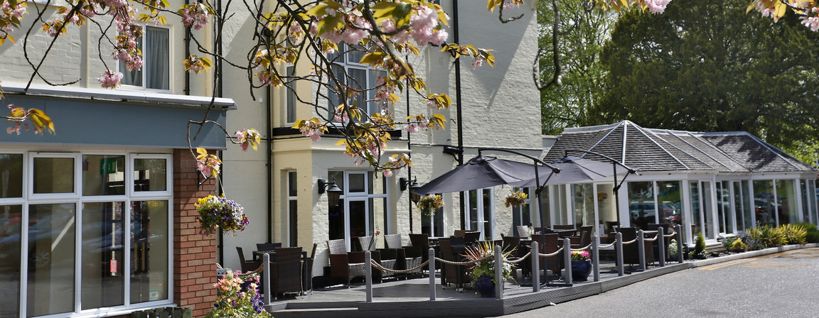 Best Western TIllington Hall Hotel building photo with open air decking eating area on show, restaurant, entrance, framed by blossoms of the tree