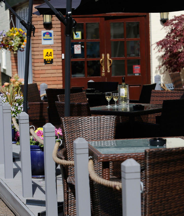 Outside seating area decking photo with wicker tables and chairs, ashtrays, alcoholic drinks, glass tables