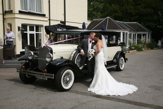 Bride and groom kissing photo with old fashioned motor car, restaurant, treeline and Best Western Tillington Hall Hotel
