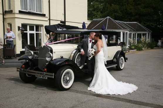 Bride and groom kissing photo with old fashioned motor car, restaurant, treeline and Tillington Hall Hotel