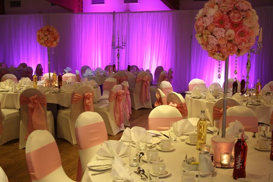 Table layout for wedding guests photo with elaborate floral decorations, pink colour scheme, drapery, chair coverings and laid tables