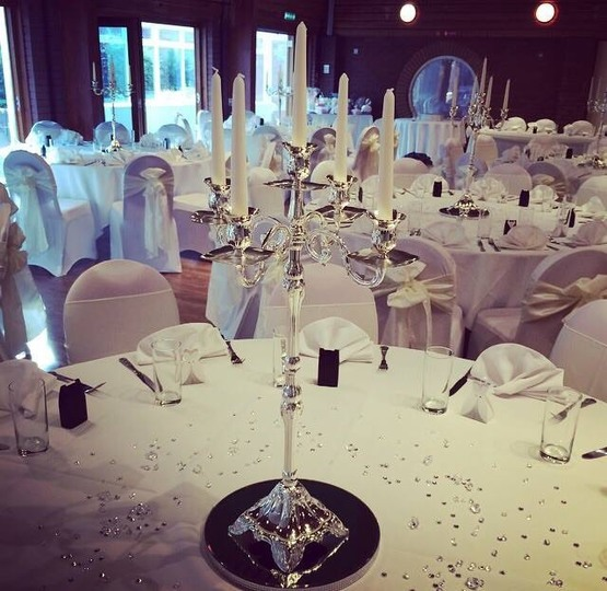 Wedding guest table layout photo with candelabrum showcased prominently, jewel table decorations, black, silver and white colour scheme, light streaming through windows