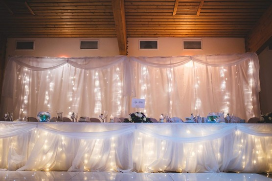 Wedding Top Table photo with white LED fairy lights, white drapery, bouquet flower arrangement between bride and groom seats