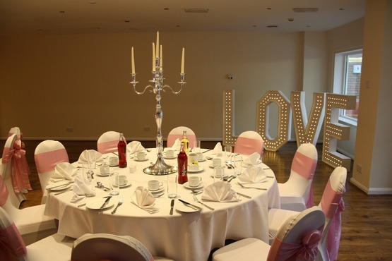 Wedding table layout photo showcasing candelabra centre piece, white and pink colour scheme, chair coverings, LOVE LED display signage