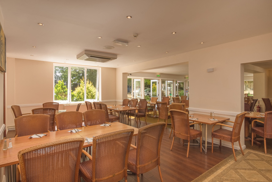 Tillington Hall Hotel Restaurant set up for lunch, at each table is a set of comfy wicker chairs to sit on