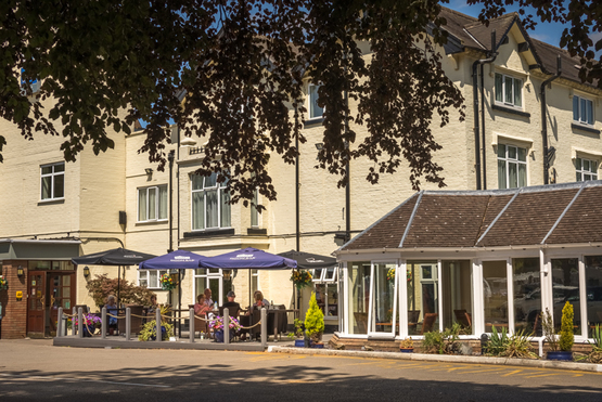 Tillington Hall Hotel front of building in bright sunny afternoon light, people sat eating and drinking on the decking outdoor eating area, framed by trees