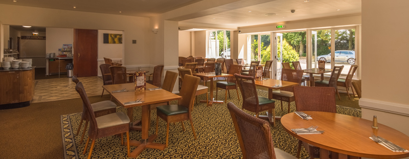Best Western Tillington Hall Hotel bistro showing patterned carpeted floor,  wicker chairs,  bright and airy environment