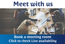 "An image from a birds-eye view showing business men and women around a boardroom table debating and discussing plans framed by copy that reads ""Meet with us - Book a meeting room, Click to check Live Availability"""