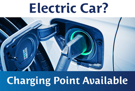 "An image of a white electric car charging bordered by copy that reads ""Electric Car? Charging Point Available"""