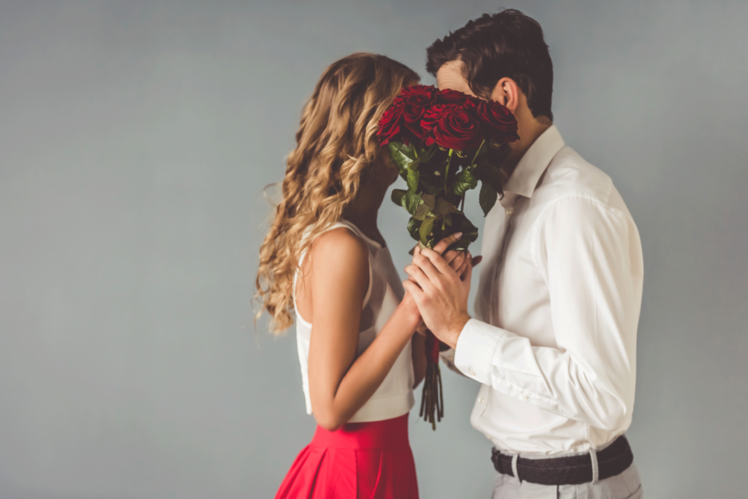 A couple hiding their faces behind a bouquet of red roses for Valentine's Day.