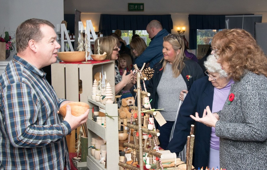 An image of a woodturner selling his wears at a Chase Handmade Craft Fair