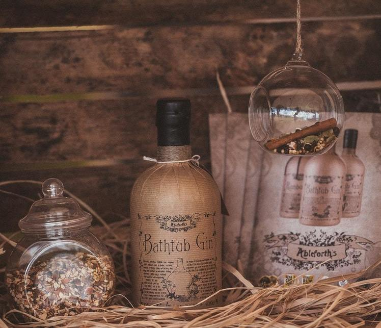 An image of Bathtub Gin nestled in some straw surrounded by jars of oats, cinnamon and fruit.