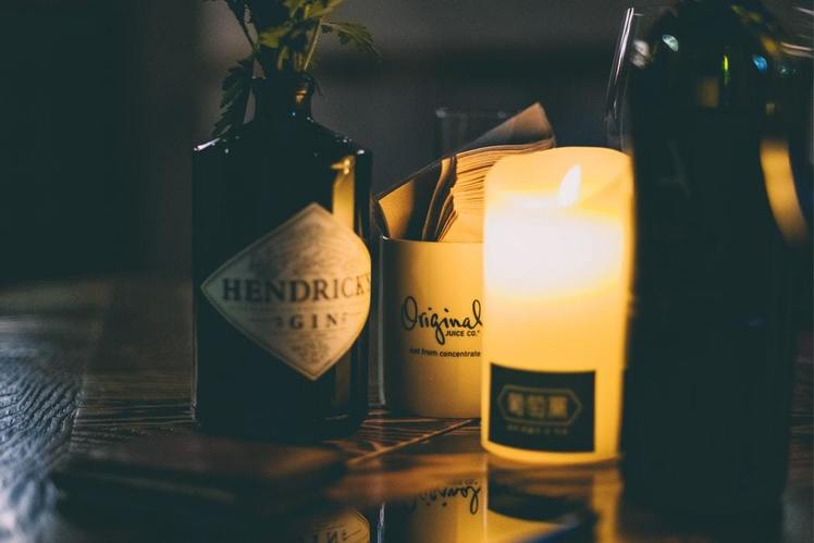 An image example of Hendrick's Gin in low light, lit by candles.