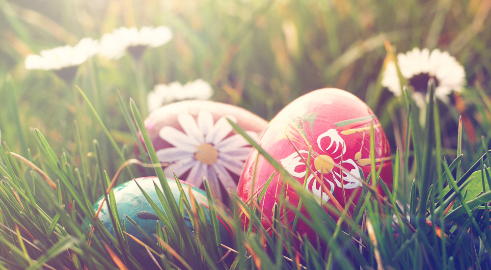 An image of decorated Easter Eggs sat in the grass during Easter Sunday