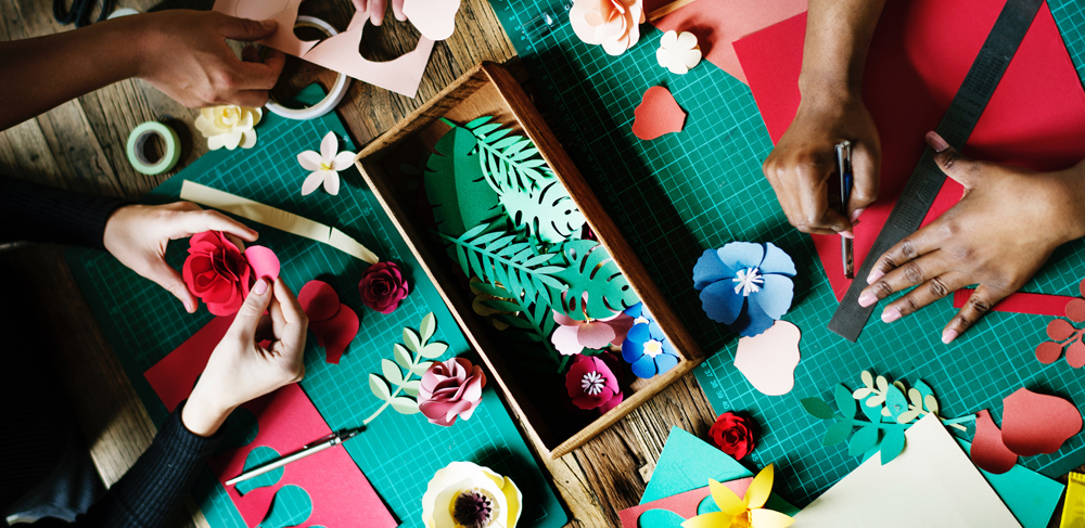 An image showing people creating papercraft artworks including flowers