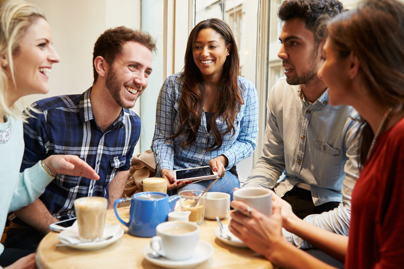 An image showing a bunch of friends sat around a table drinking coffee and tea. They're all grinning and laughing. Behind them bright light streams in.