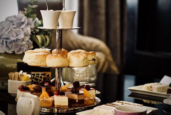 Traditional Afternoon Tea photograph showing cakes, scones, preserves and creams