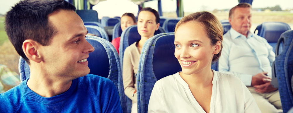 An image of happy people riding a coach