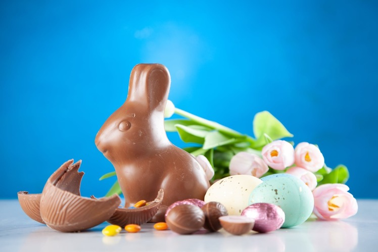 A chocolate easter egg has been cracked open. Beside it is a chocolate bunny and some chcoolate mini-eggs to symbolise Easter.