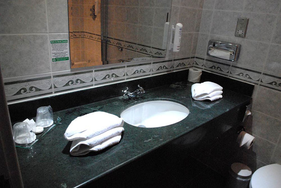 Bathroom suite photo with marble countertops, enamel sinks, large mirror,  arranged towels and toiletries